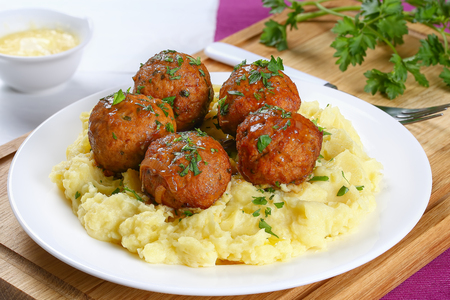 delicious meatballs on hot potato puree with cheese sauce on background, view from above, close-up Stock Photo