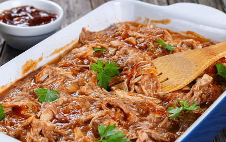 delicious Shredded meat tossed in barbecue sauce in dish with wooden fork spatula, on old wooden table with sauce on background, close-up, macro, selective focus
