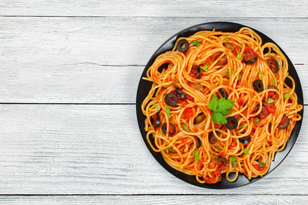 Delicious Spaghetti alla puttanesca with capers. olives, tomato sauce sprinkled with parsley on black plate on wooden table, authentic basic recipe, view from above Stock Photo