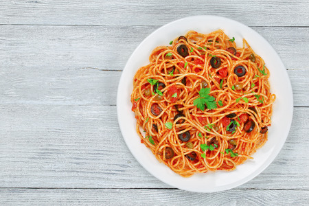 Delicious Spaghetti with capers. olives, anchovies, tomato sauce sprinkled with parsley on white plate on wooden table, authentic basic recipe, view from above