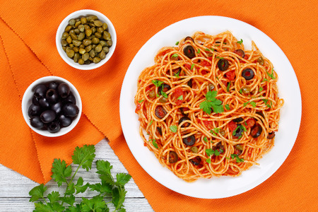 Delicious Spaghetti alla puttanesca with capers, olives, anchovies, tomato sauce sprinkled with parsley on white plate on table mat with olive and capers in bowls, authentic recipe, view from above