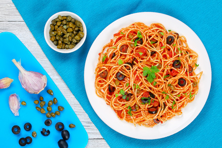 Pasta spaghetti with tomato sauce, capers and olives on plate with ingredients on cutting board on  wooden background, traditional Italian recipe view from above