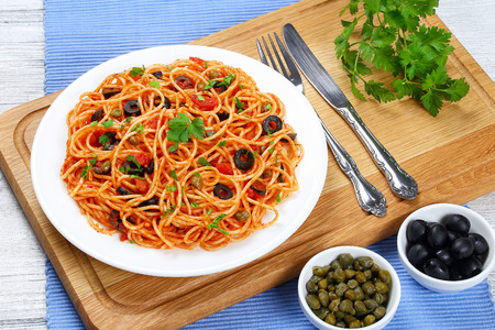 Spaghetti di pasta con salsa di pomodoro, capperi e olive sul piatto sul tagliere di legno con forchetta e coltello, vista ricetta tradizionale italiana dall'alto, close-up