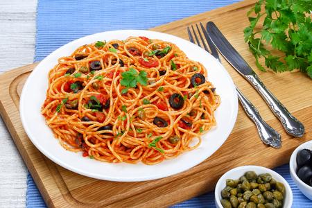 Espagueti de pasta con salsa de tomate, alcaparras y aceitunas en la placa en tabla de cortar de madera con tenedor y cuchillo, receta tradicional italiana vista desde arriba, primer plano Foto de archivo