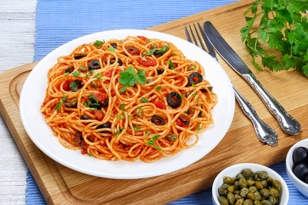 Pasta spaghetti with tomato sauce, capers and olives on plate on  wooden cutting board with fork and knife, traditional Italian recipe view from above, close-up Stock Photo