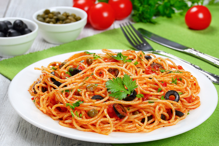 Pasta spaghetti with tomato sauce, capers, anchovy and olives on plate with fork and knife on green table mat and ingredients on background, authentic Italian recipe view from above, close-up