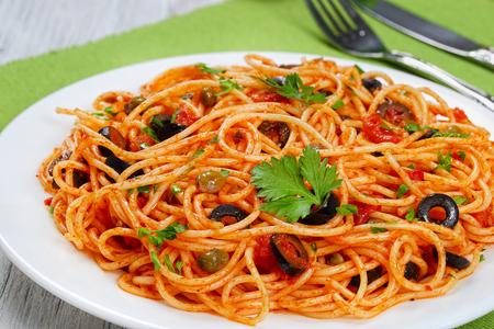 Pasta spaghetti con salsa de tomate, alcaparras, anchoa y aceitunas en plato con tenedor y cuchillo sobre estera de mesa verde, auténtica receta italiana vista desde arriba, close-up Foto de archivo