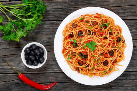 Delicious Spaghetti alla puttanesca with capers, olives, anchovies, tomato sauce sprinkled with parsley on white plate on wooden table with ingredients, authentic basic recipe, view from above Stock Photo