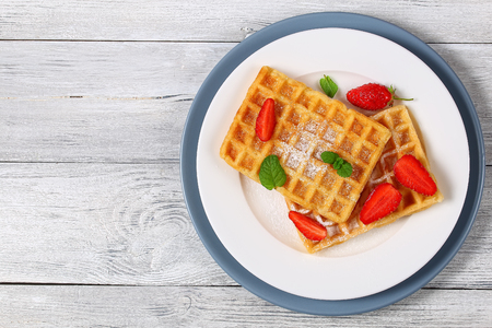 biscuits: Belgian waffles with strawberries and powdered sugar on a plate
