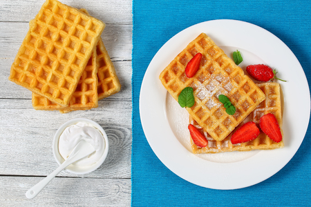 Belgian waffles with strawberries and powdered sugar on a plate