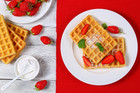 hotcakes: Belgian waffles with strawberries and powdered sugar on a plate