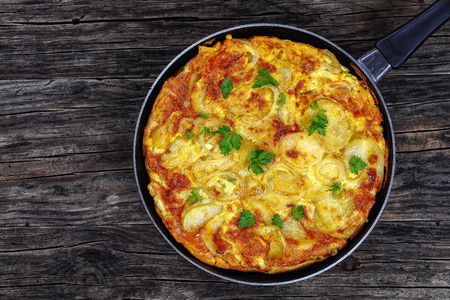 Tortilla de patatas sprinkled with parsley in skillet on dark wooden table, traditional spanish dish. Omelette with eggs, potatoes and onion, authentic recipe, view from above