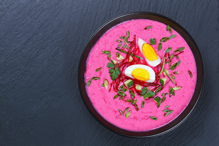 delicious Cold yogurt beetroot soup with cucumber, scallions, radish decorated with boiled egg cut un slices  and parsley in black bowl on slate tray, view from above