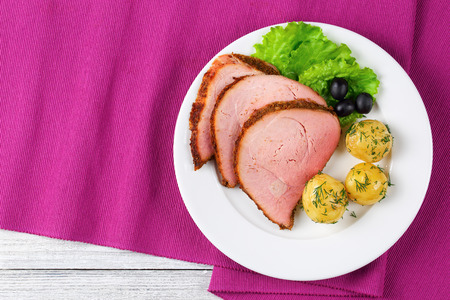 delicious spicy Beef Roast cut in slices on white plate served with new potatoes,   fresh green lettuce salad and black olives on restaurant table mat, view from above