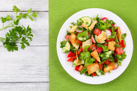 delicious Fattoush or bread salad with pita croutons, fresh vegetables and herbs,  on white plate on wooden table, easy and healthy authentic recipe, view from above