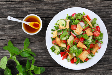 Fattoush or bread salad with pita croutons, fresh vegetables and herbs,  on white plate on wooden table with sumac, lemon, olive oil gravy, easy and healthy authentic recipe, view from above