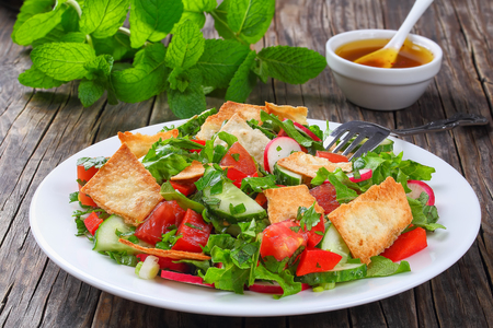 delicious traditional Fattoush or bread salad with pita croutons, cucumber, tomato, lettuce and herbs on white plate. fresh mint and oil, lemon, sumac dressing on background, view from above, close-up