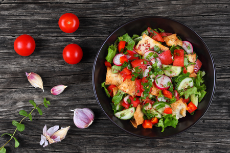 delicious traditional lebanese Fattoush or bread salad with pita croutons, cucumber, tomato, lettuce and herbs in  black bowl on wooden table, authentic recipe, view from above