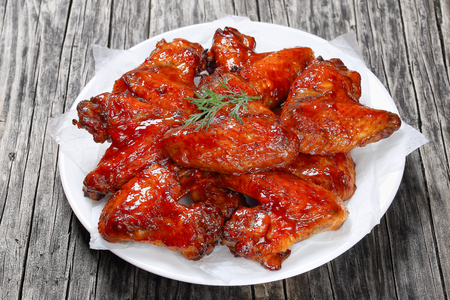 close-up of delicious crispy roasted chicken wings on plate on dark wooden table with barbecue sauce and lemon wedges, view from above