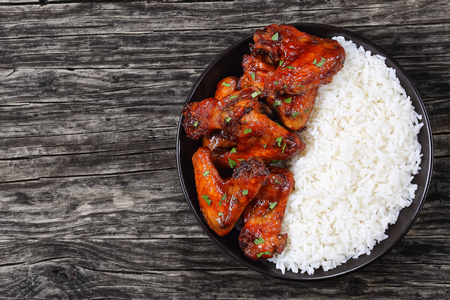 sprinkled: rice with delicious honey garlic ginger glazed chicken wings sprinkled with parsley in black bowl on dark wooden table, view from above Stock Photo