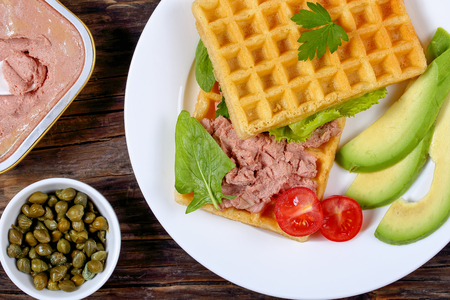 caper: salted belgian waffles sandwich with avocado, meat mushrooms and liver pate, lettuce, spinach, tomatoes on white plate on dark wooden table,can with pate and capers on background, view from above