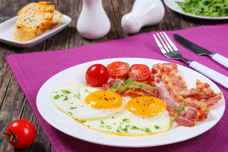 crispy fried bacon, Sunny Side Up Eggs, arugula and tomatoes on white plate on dark table, french baguette toasts, salt and pepper shakers on background, view from above, close-up Stock Photo