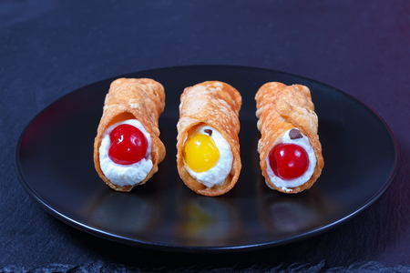 delicious homemade Sicilian Cannoli - traditional Italian Dessert, filling with ricotta cheese on black plate on dark slate tray, authentic classic recipe, view from above, close-up Stock Photo