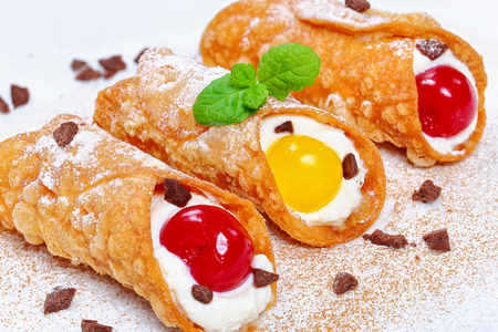 italian dessert - Sicilian Cannoli, filling with ricotta cheese cream and cherries on white table sprinkled with chocolate powder, authentic italian recipe, top view, close-up