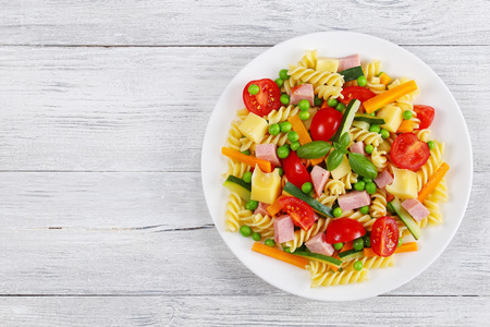 cold cut: delicious salad of italian pasta fusilli with carrot and zucchini sticks, ham, cheese chunks, green peas, cherry tomatoes on white plate on wooden table, view from above Stock Photo