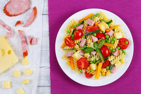 cold cut: light healthy salad of italian pasta fusilli with carrot and zucchini sticks, ham, cheese, green peas, cherry tomatoes on white plate on table mat with ingredients on paper, view from above Stock Photo