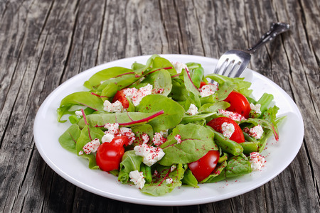 delicious healthy low calories salad of green beans, chard, arugula, tomato and cottage cheese, sprinkled with sumac on white plate, on dark wooden table, view from above, close-up Stock Photo