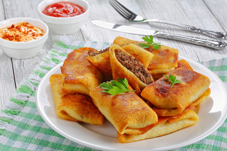 rolled up delicious Crepes stuffed with minced liver and meat on white plate on old wooden table with sauceon background view from above, close-up