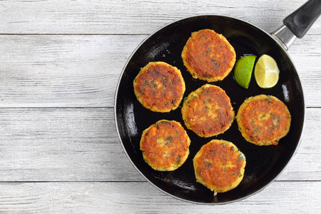 delicious fresh fried fish cakes on skillet with lime slices, authentic recipe, view from above 免版税图像