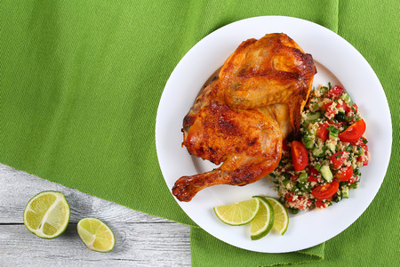 half of delicious grilled juicy chicken with golden brown crust served with lime slices and couscous vegetable salad on white plate on  green table mat, view from above