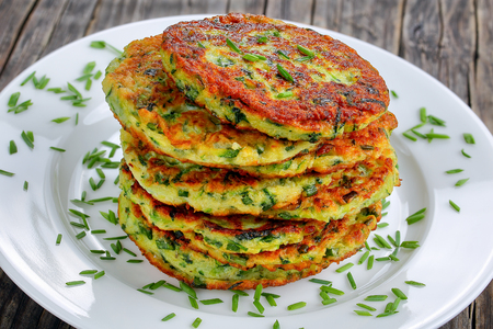 crispy zucchini fritters sprinkled with finely chopped chives on platter, on old dark wooden table, vegetarian recipe, horizontal view from above