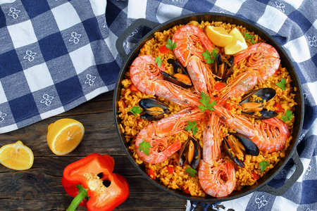 delicious seafood valencia paella with king prawns, mussels on savory creamy saffron rice with spices and lemon wedges in pan, on wooden table, view from above