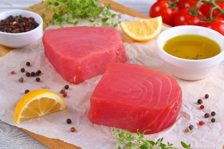 close-up of delicious Fresh raw tuna fish steaks prepared for cooking on cutting board with thyme leaves, lemon slices. olive oil and cherry tomatoes on background, view from above Stock Photo