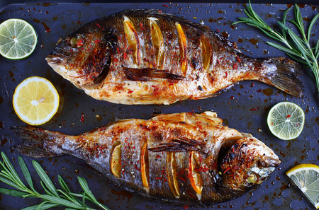 gilt head: delicious roasted dorado or Gilt-head bream fish with lemon and orange slices, spices, and fresh rosemary on baking sheet, view from above, close-up Stock Photo