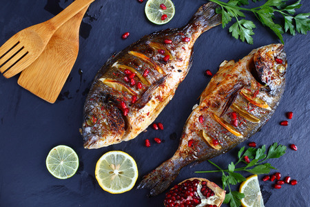 delicious roasted spicy Gilthead seabream fish with lemon slices and fresh parsley, pomegranate seeds on slate tray with wooden shovels,  horizontal view from above