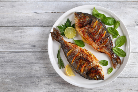 delicious grilled dorado or sea bream fish with lemon and orange slices, spices, fresh parsley and spinach on white platter on old wooden table, horizontal view from above Stock Photo