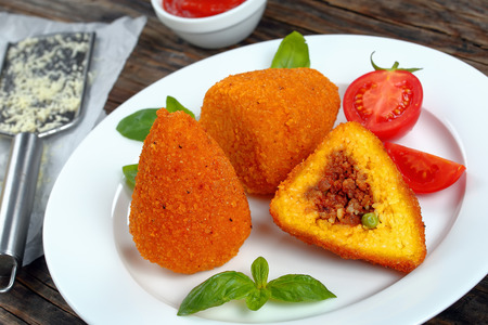 fried arancini - classic italian cuisine, risotto cones stuffed with meat ragu, and green peas on white plate, tomato sauce, parmesan cheese on table, authentic recipe,  view from above, close-up