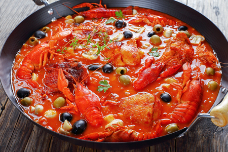 close-up of chicken marengo - chicken meat stew with crawfishies, chopped tomato sauce, onion, mushrooms, olives, thyme in skillet on wooden kitchen board, holiday recipes, view from above Stock Photo