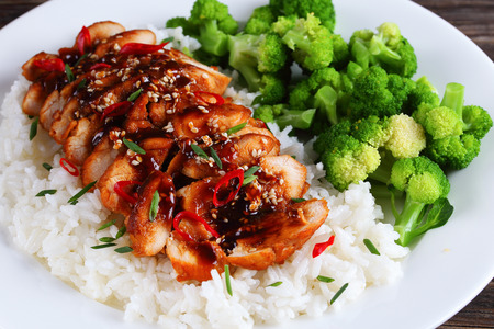 delicious teriyaki chicken breast cut in slices served with white rice and steamed broccoli on white plate.on wooden table, view from above, close-up