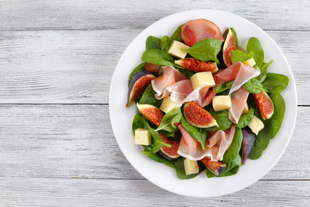 delicious healthy salad of fresh spinach, figs, thinly sliced prosciutto and tender mozzarella cheese on white plate on wooden table, view from above, blank space left