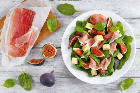 fresh baby spinach, figs, thinly sliced italian ham and tender mozzarella cheese salad on white plate on wooden table with ingredients on background, view from above