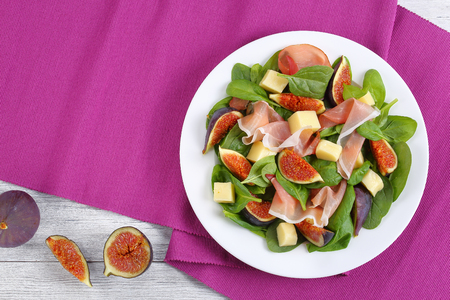 fresh baby spinach, figs, thinly sliced italian ham and tender mozzarella cheese salad on white plate  on table mat on wooden kitchen table, view from above Stock Photo