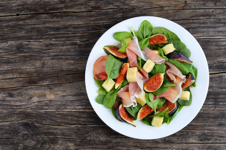 spinach, figs, thinly sliced italian ham and tender mozzarella cheese salad on white plate on dark wooden kitchen table, view from above Stock Photo