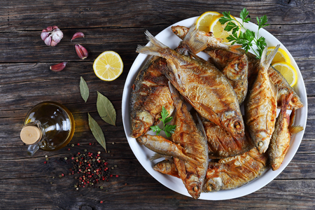 delicious hot fried mix of freshwater fish marinated with lemon slices, bay leaf, spices on white platter on old dark rustic table, horizontal view from above
