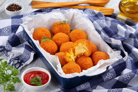arancini - saffron rice balls stuffed with cheese in baking dish on old wooden table with kitchen towel, tomato sauce, olive oil and shovels on background, horizontal view from above, close-up