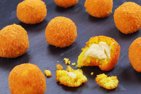 delicious hot italian arancini - saffron rice balls stuffed with melted cheese on black slate tray,  view from above, close-up Foto de archivo